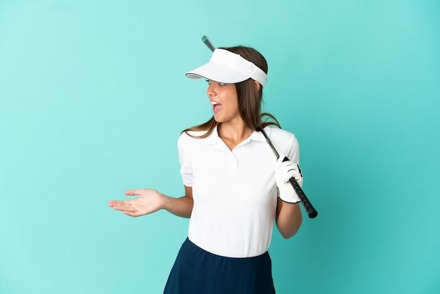 Frau, die golf über isoliertem blauem hintergrund mit überraschungsausdruck spielt, während sie zur seite schaut