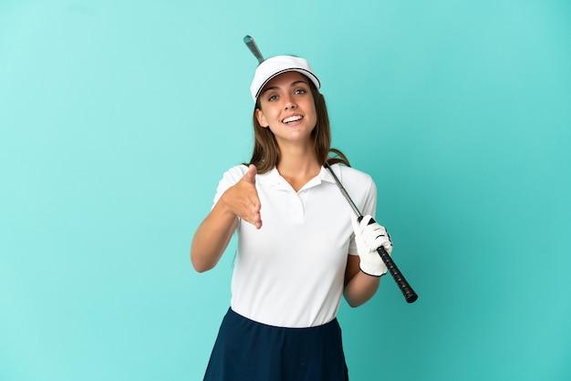 Frau, die golf über isoliertem blauem hintergrund spielt und sich die hände schüttelt, um ein gutes geschäft abzuschließen?