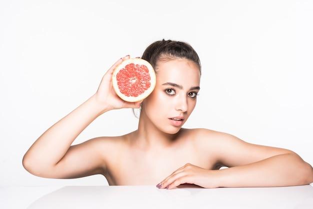 Frau, die grapefruit hält