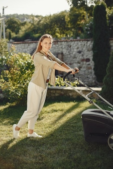 Frau, die gras mit rasenmäher im hinterhof schneidet. dame auf einem gras.