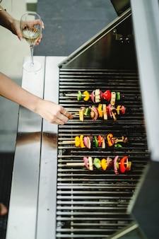 Frau, die grill des strengen vegetariers auf einem holzkohlegrill kocht