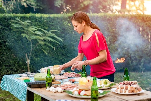 Frau, die grilltreffen auf einem holztisch vorbereitet