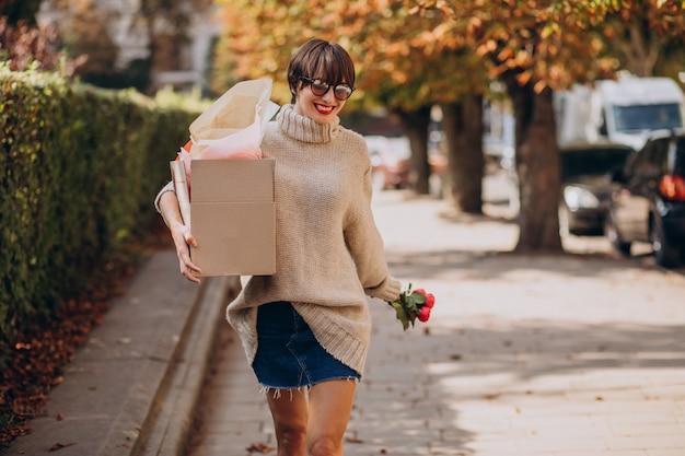 Frau, die große paketbox hält und in der straße geht