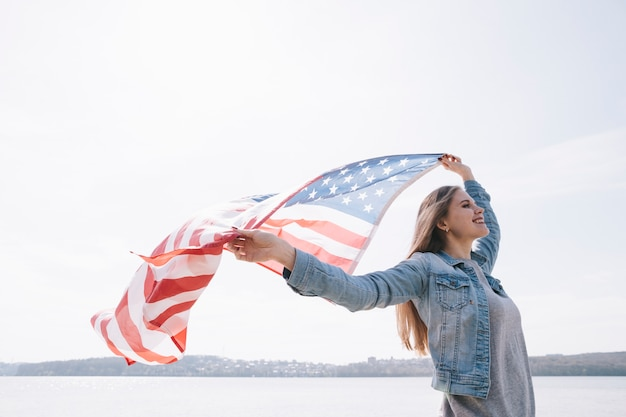Frau, die große usa-flagge wellenartig bewegt