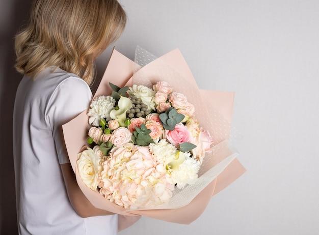 Frau, die großen blumenstrauß von hortensien, rosen hält