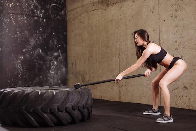 Frau, die großen reifen mit vorschlaghammer während des intensiven trainings im fit-fitnessstudio zerschmettert