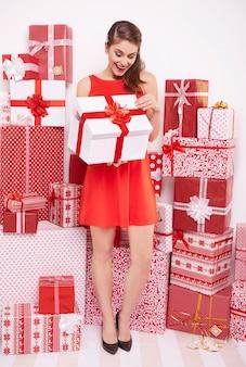 Frau, die großes weißes geschenk öffnet