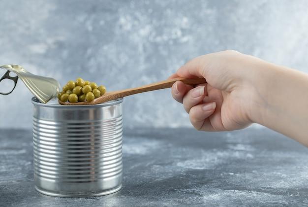Frau, die grüne erbsen von der dose mit löffel über grauem tisch nimmt.