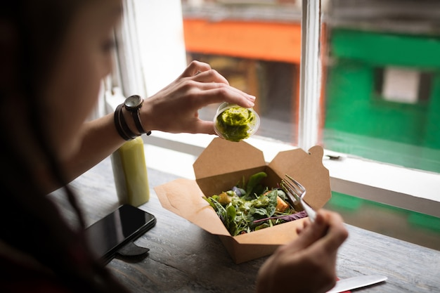 Frau, die grüne soße auf einen salat gießt
