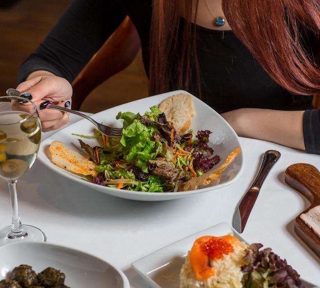 Frau, die grünen salat mit chips und einem glas prosecco isst.