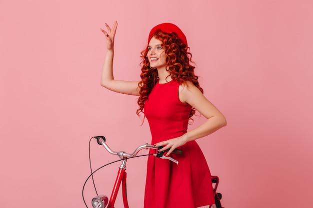 Frau, die gruß beim sitzen auf dem fahrrad auf rosa raum winkt. dame in roter baskenmütze und kleid.