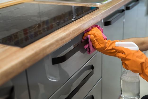 Frau, die gummihandschuhe trägt und die küchenschränke oder die oberfläche reinigt. reinigungskonzept