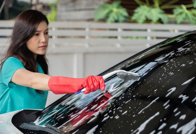 Frau, die gummiwalze verwendet, um windschutzscheibe des autos zu waschen