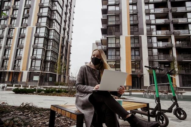 Frau, die gute zeit auf bank im park nahe der wohnung ihres freundes verbringt. sie tätigt einen videoanruf, arbeitet an ihrem laptop und schaut weg. zwei elektroroller stehen in der nähe. schnelles reisekonzept.