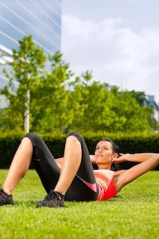 Frau, die gymnastik des grases in der stadt tut