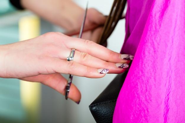 Frau, die haarschnitt vom friseur oder vom stilisten empfängt