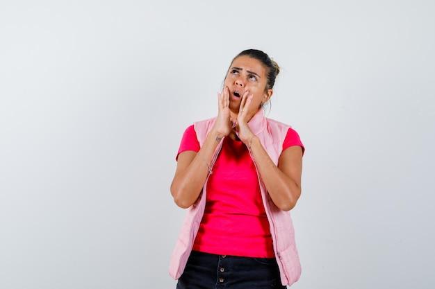 Frau, die händchen nahe offenem mund in t-shirt, weste hält und überrascht schaut