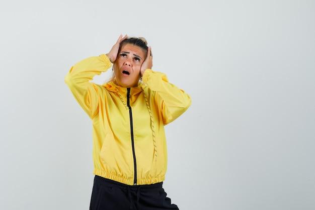 Frau, die hände auf kopf im sportanzug hält und wehmütig, vorderansicht schaut.