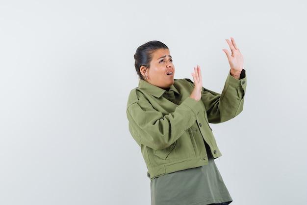 Frau, die hände auf schützende weise in jacke, t-shirt anhebt und ängstlich aussieht.
