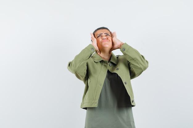 Frau, die hände hinter kopf in jacke, t-shirt hält und genervt schaut