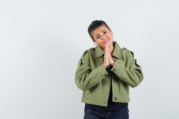 Frau, die hände in der gebetsgeste in der jacke, im t-shirt hält und hoffnungsvoll aussieht