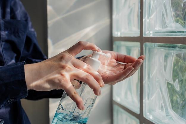 Frau, die hände mit einem händedesinfektionsgel reinigt, um eine coronavirus-kontamination zu verhindern