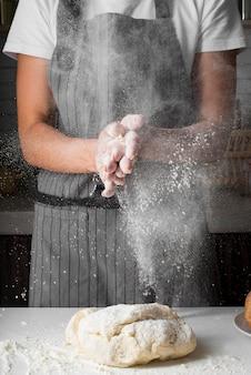 Frau, die hände mit mehl über teig klatscht