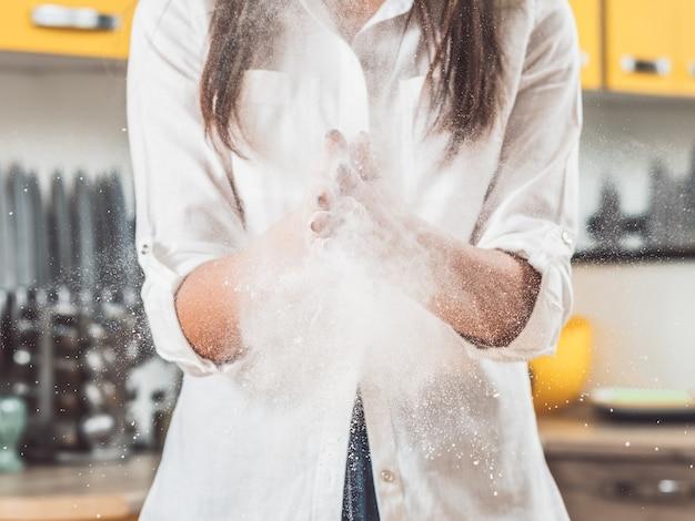 Frau, die hände voll mehl fasst. explosion von weißem pulver