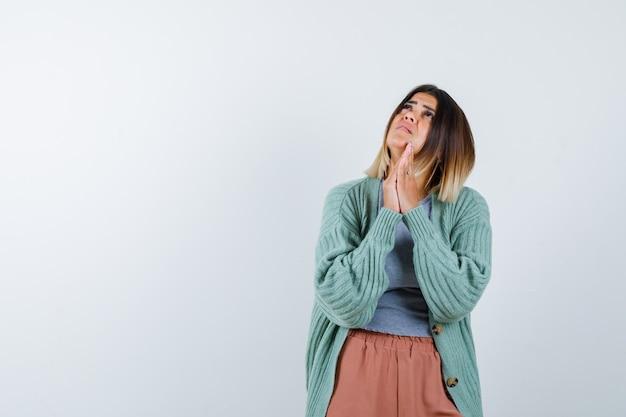 Frau, die hände zusammen drückt, während sie in freizeitkleidung betet und hilflos aussieht. vorderansicht.