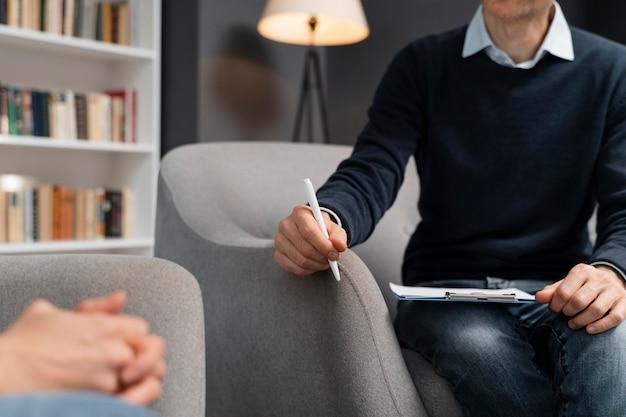 Frau, die hände zusammenhält, die mit therapeut sprechen