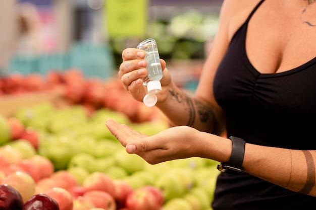 Frau, die händedesinfektionsmittel, lebensmitteleinkaufsbild verwendet