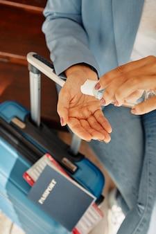 Frau, die händedesinfektionsmittel während am flughafen mit gepäck während der pandemie verwendet