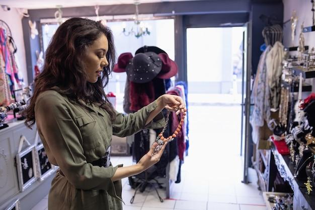 Frau, die halskette in der schmuckabteilung auswählt