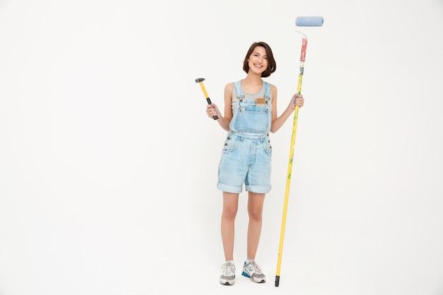 Frau, die hammer und malpinsel hält, haus renovierend