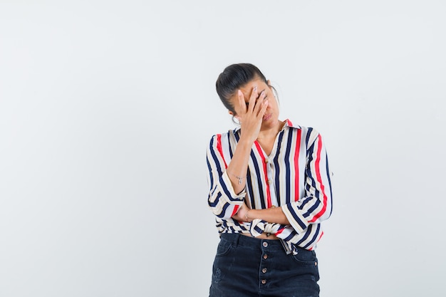 Frau, die hand auf gesicht in hemd, rock hält und müde aussieht