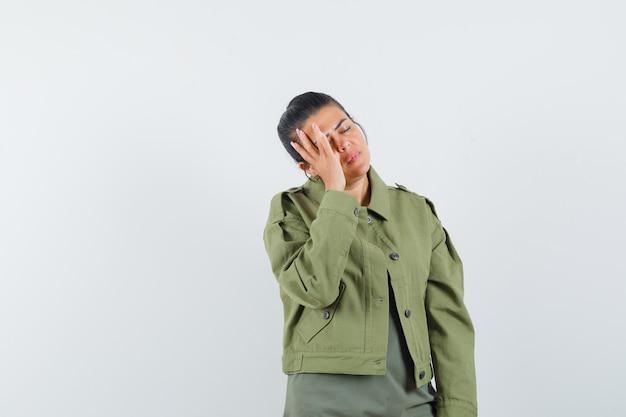 Frau, die hand auf gesicht in jacke, t-shirt hält und müde aussieht.