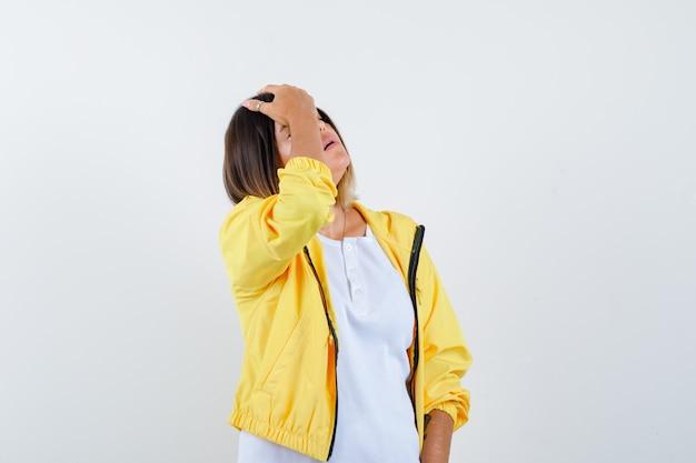 Frau, die hand auf kopf in t-shirt, jacke hält und vergesslich aussieht. vorderansicht.