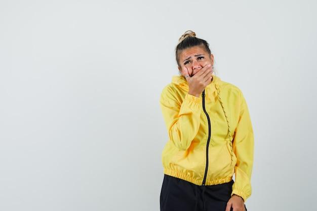 Frau, die hand auf mund im sportanzug hält und deprimiert, vorderansicht schaut.