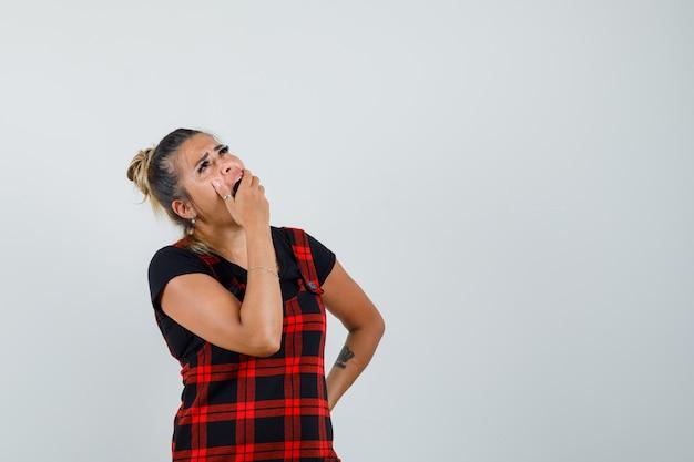 Frau, die hand auf mund im trägerkleid hält und hilflos schaut, vorderansicht.