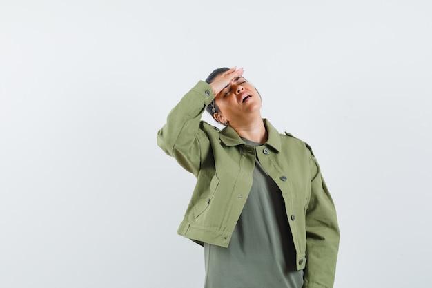 Frau, die hand auf stirn in jacke, t-shirt hält und müde aussieht