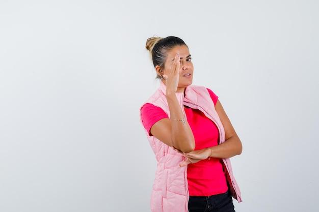 Frau, die hand hält, um gesicht in t-shirt, weste und beschämt zu bedecken
