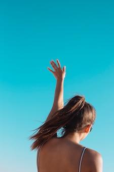 Frau, die hand im himmel spinnt