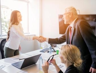 Frau, die Hand mit älterem Geschäftsmann rüttelt, nachdem die Sitzung beendet worden ist