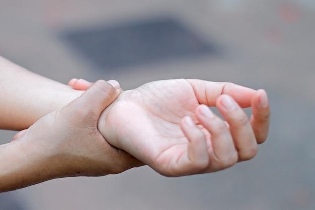 Frau, die hand zum fleck des handgelenksschmerzes hält