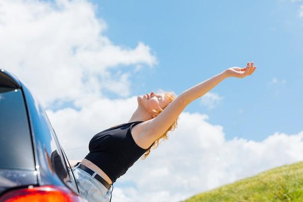 Frau, die hand zum himmel aus autofenster am sonnigen tag heraus anhebt