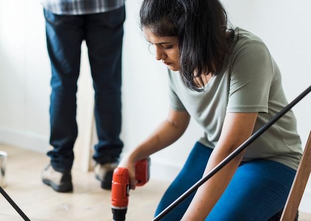 Frau, die handbohrmaschine verwendet, um einen holztisch zusammenzubauen