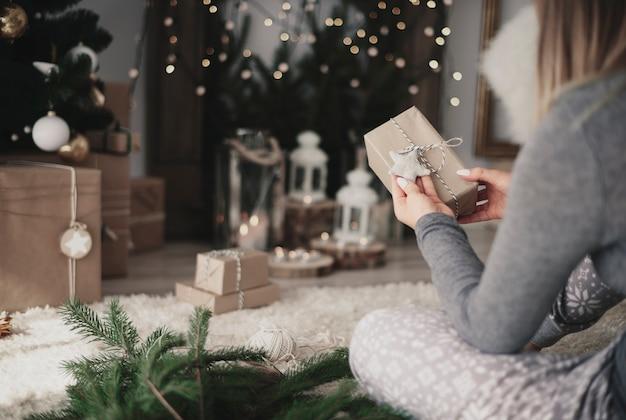 Frau, die handgemachte weihnachtsgeschenke beobachtet