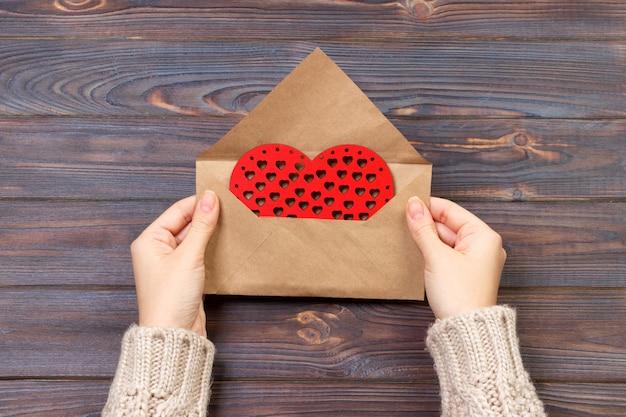 Frau, die handgemachten umschlag für die verpackung am valentinstag vorbereitet. valentinstag-konzept