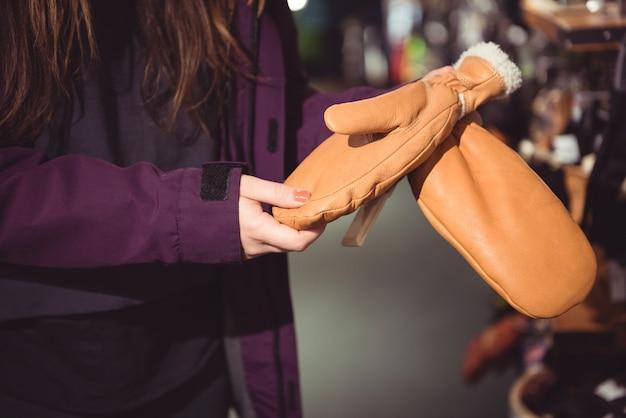 Frau, die handschuh in einem geschäft auswählt