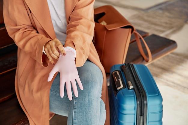 Frau, die handschuhe am flughafen während der pandemie anzieht
